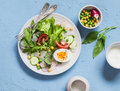 Fresh vegetable salad with tomatoes, radish, green herbs and boiled egg on a light blue stone background. Royalty Free Stock Photo
