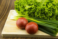 Fresh vegetables on the chopping board counter onions tomatoes cabbage are we often eat Stock Photo