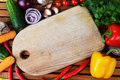 Fresh vegetables and cutting board on wooden background Stock Photography