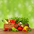 Fresh vegetables and herbs over green background on wooden table nature raw food ingredients shopping basket Royalty Free Stock Image
