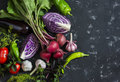 Fresh vegetables - red cabbage, beets, eggplant, peppers, garlic, tomatoes, herbs on a dark background. Raw ingredients. Royalty Free Stock Photo