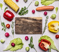 Fresh vegetables tomatoes peppers basil parsley corn salad laid out around a cutting board wooden rustic background top v on view Stock Photo