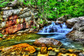 Fresh water cascading over large rocks in a small stream HDR. Royalty Free Stock Photo