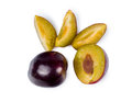 Fresh whole halved and sliced plums purple for a healthy dessert on a white background overhead view Stock Photography