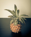 Fresh whole pineapple on a black table near white wall. Toned Royalty Free Stock Photo