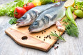 Fresh whole sea basses a cutting board Royalty Free Stock Photos