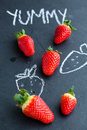 Fresh whole strawberries chalk drawings yummy word dark background Stock Photography