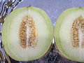Fresh yellow cantaloupe cut in half on the old tray in  closeup Royalty Free Stock Photo