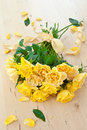 Fresh yellow roses with a checkered ribbon on wooden table Stock Photo
