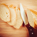 Freshly baguette sliced on wooden cutting board baked knife top view vintage stylized Stock Image