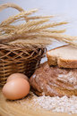 Freshly baked bread crusty on the table with a basket of ears and eggs Stock Image