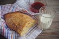 Freshly baked bread served with jam and glass of milk slice whole grain loaf a rustic wooden table top Stock Photo