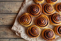 Freshly baked cinnamon buns with spices and cocoa filling on parchment paper. Sweet Homemade Pastry christmas baking. Royalty Free Stock Photo