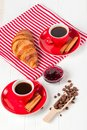 Freshly baked croissant on napkin, cup of coffee in red cup on white wooden background. French breakfast. Fresh pastries for break Royalty Free Stock Photo