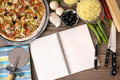 Freshly baked pizza with cookbook blank notebook or surrounded by various ingredients Royalty Free Stock Image