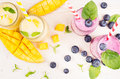 Freshly blended yellow and violet fruit smoothie in glass jars with straw, mint leaves, mango slices and berry, close up, top vie Royalty Free Stock Photo