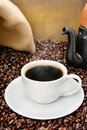 Freshly brewed coffee cup over roasted beans Stock Photography