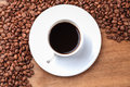 Freshly brewed espresso closeup and coffee beans on old wooden table Royalty Free Stock Photos