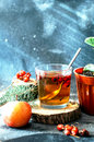 Freshly brewed tea in glass cup on blue background orange hot drink selective focus fresh herbal tea with tincture of red berri Stock Photos