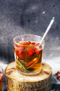 Freshly brewed tea in glass cup on blue background orange hot drink selective focus fresh herbal tea with tincture of red berri Royalty Free Stock Images