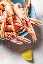 Freshly cooked scampi in a blue bowl with lemon on old wooden table Stock Image