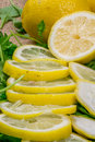 Freshly cut lemons with green salad leaves close up Royalty Free Stock Photo