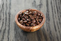 Freshly roasted arabica coffee beans in bowl on wood table Royalty Free Stock Photography