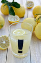 Freshly squeezed lemon juice lemons in a glass with a exclamation on light wood background close up Stock Photography