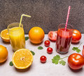 Freshly squeezed orange juice, sliced oranges, tomato juice with diced tomatoes wooden rustic background top view close up Royalty Free Stock Photo