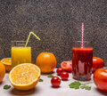 Freshly squeezed orange juice, sliced oranges, tomato juice with diced tomatoes on wooden rustic background top view close up Royalty Free Stock Photo