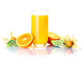 Freshly squeezed orange juice tall glass of colourful with sliced fresh oranges limes and cape gooseberries in a vivid still life Stock Image