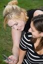 Freunde auf Handy zusammen (schöne junge Blondine und Brune Lizenzfreie Stockfotos