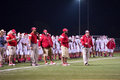 Friday night lights coaches on sideline of a high school football game Royalty Free Stock Image