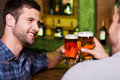 Friday night out two cheerful young men toasting with beer and smiling while sitting together at the bar counter Royalty Free Stock Photo