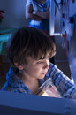 Fridge raid hungry little boy raids the refridgerator late at night unaware that his mother is watching Stock Image