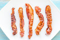 Fried bacon strips on the square plate close up Stock Photo