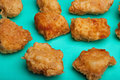 Fried boneless chicken wings breaded on turquoise surface Stock Photo