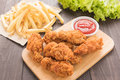 Fried chicken drumstick and french fries on wooden table Royalty Free Stock Images