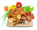 Fried chicken and fresh vegetables on cutting board on white bac legs a a background close up horizontal photo Stock Image
