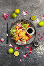 Fried chicken with soy sauce and vegetables on a black plate, view from the top Royalty Free Stock Photo