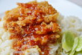 Fried chicken on steamed rice dressing sweet chili sauce on dish