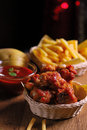 Fried chicken wings with french fries and ketchup on wooden table Royalty Free Stock Image