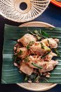 Fried chicken wings in Thai northeastern style with garlic and kaffir lime leaves served on banana leaf