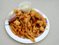 Fried conch fritters and french fries with coleslaw on a paper plate Stock Photo