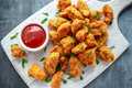 Fried crispy chicken nuggets with ketchup on white board Royalty Free Stock Photo