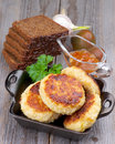 Fried cutlets arrangement of delicious chicken meat in black saucepan with brown bread bell pepper sauce and vegetables closeup on Stock Image