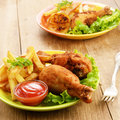 Fried drumsticks with french fries Stock Photos