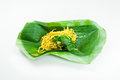 Fried dry yellow noodles on a banana leaf on white background