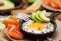 Fried egg, avocado and smoked salmon in frying pan Royalty Free Stock Photo