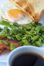 Fried egg, bacon, green beans, toastsand white cup of coffee on light background. English breakfast. Royalty Free Stock Photo